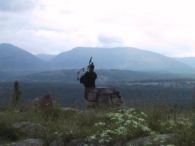 Lone piper in the Scottish hills