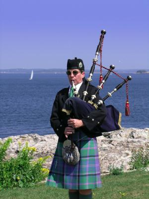 piper playing bagpipes by the sea in Scotland